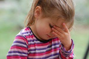 Migräne bei Kindern - Mädchen hat Kopfschmerzen